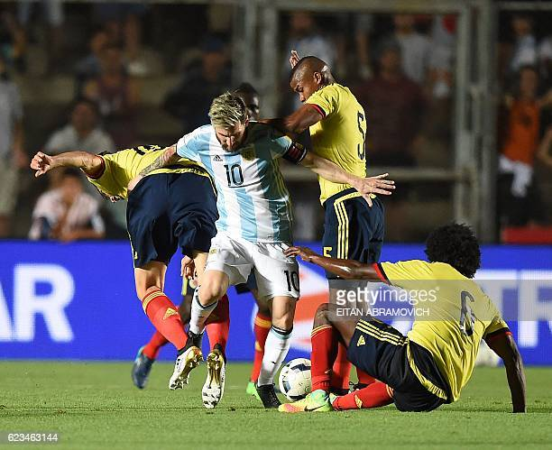 TOPSHOT Argentina's Lionel Messi struggles for the ball with Colombia's midfielder Wilmar Barrios and Colombia's midfielder Carlos Sanchez during...