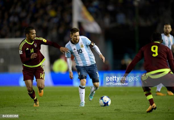 Argentina's Lionel Messi vies for the ball with Venezuela's Yangel Herrera and Venezuela's Sergio Cordova during their 2018 World Cup football...