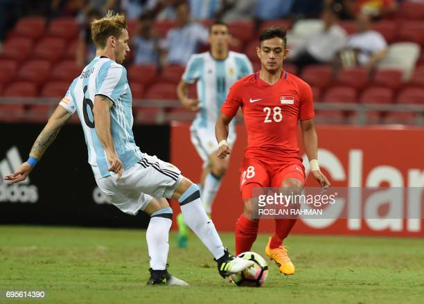 Argentina's Lucas Biglia controls the ball as a Singaporean player looks on during the international friendly football match between Singapore and...