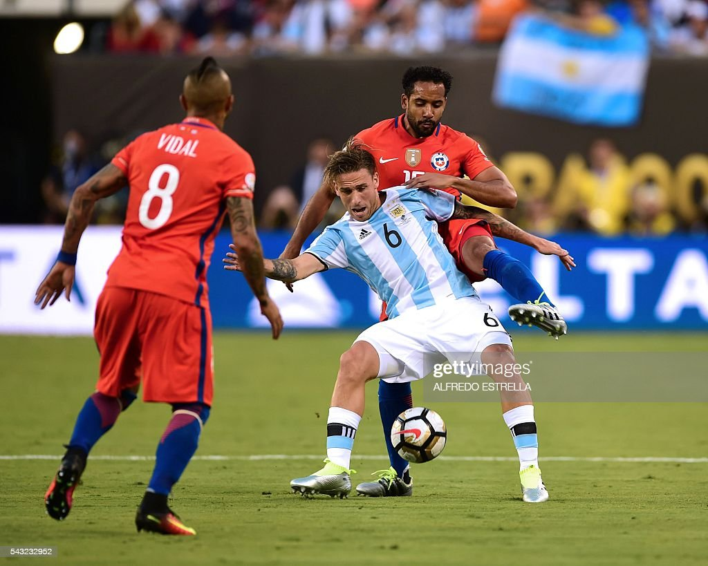 Argentina's Lucas Biglia (C) is marked by Chile's Jean Beausejour and Chile's Arturo Vidal (L) during the Copa America Centenario final in East Rutherford, New Jersey, United States, on June 26, 2016. / AFP / Alfredo ESTRELLA