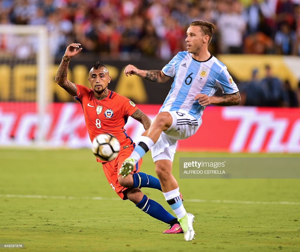 Argentina's Lucas Biglia (R) kicks the ball marked by Chile's Arturo Vidal during the Copa America Centenario final in East Rutherford, New Jersey, United States, on June 26, 2016. / AFP / Alfredo ESTRELLA