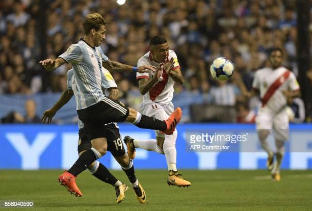 Argentina's Lucas Biglia strikes the ball next to Peru's Sergio Pena during their 2018 World Cup qualifier football match in Buenos Aires on October...