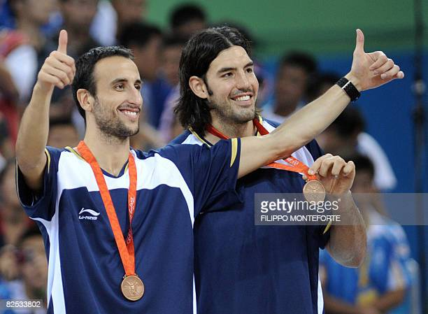 Argentina's Luis Alberto Scola and Argentina's Emanuel Ginobili celebrate on the podium after the men's basketball gold medal match of the Beijing...