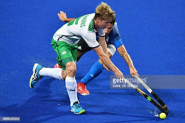 TOPSHOT Argentina's Manuel Brunet and Ireland's Kirk Shimmins vie during the mens's field hockey Ireland vs Argentina match of the Rio 2016 Olympics...