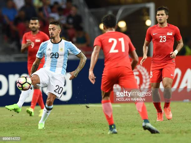 Argentina's Manuel Lanzini controls the ball as Singaporean players look on during the international friendly football match between Singapore and...