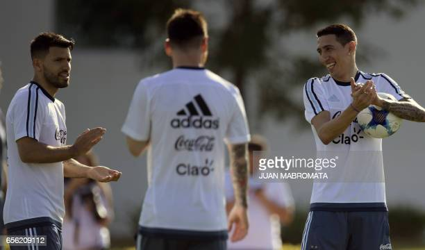 Argentina's midfielder Angel Di Maria and forward Sergio Aguero clap their hands next to forward Lionel Messi during a training session in Ezeiza...