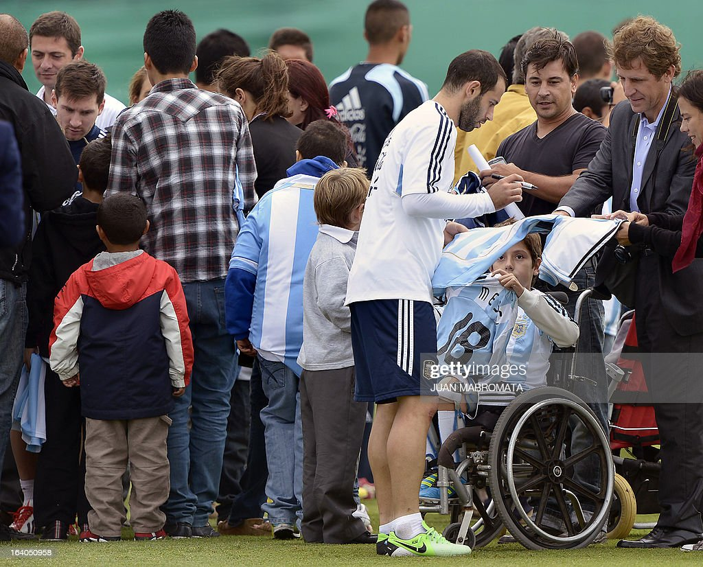 Argentina's midfielder Javier Mascherano (C) and forward Lionel Messi (2-L) sign autographs during a training session in Ezeiza, Buenos Aires on March 19, 2013 ahead of the Brazil 2014 FIFA World Cup South American qualifier football match against Venezuela on March 22. AFP PHOTO / Juan Mabromata