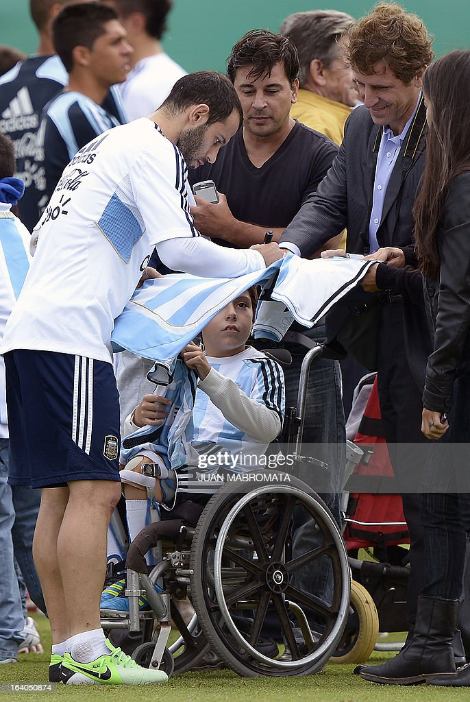 Argentina's midfielder Javier Mascherano signs a jersey during a training session in Ezeiza, Buenos Aires on March 19, 2013 ahead of the Brazil 2014 FIFA World Cup South American qualifier football match against Venezuela on March 22. AFP PHOTO / Juan Mabromata