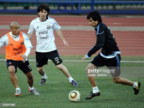 Argentina's midfielder Javier Pastore control the ball next to forward Lionel Messi and defender Clemente Rodriguez during a training session at the...