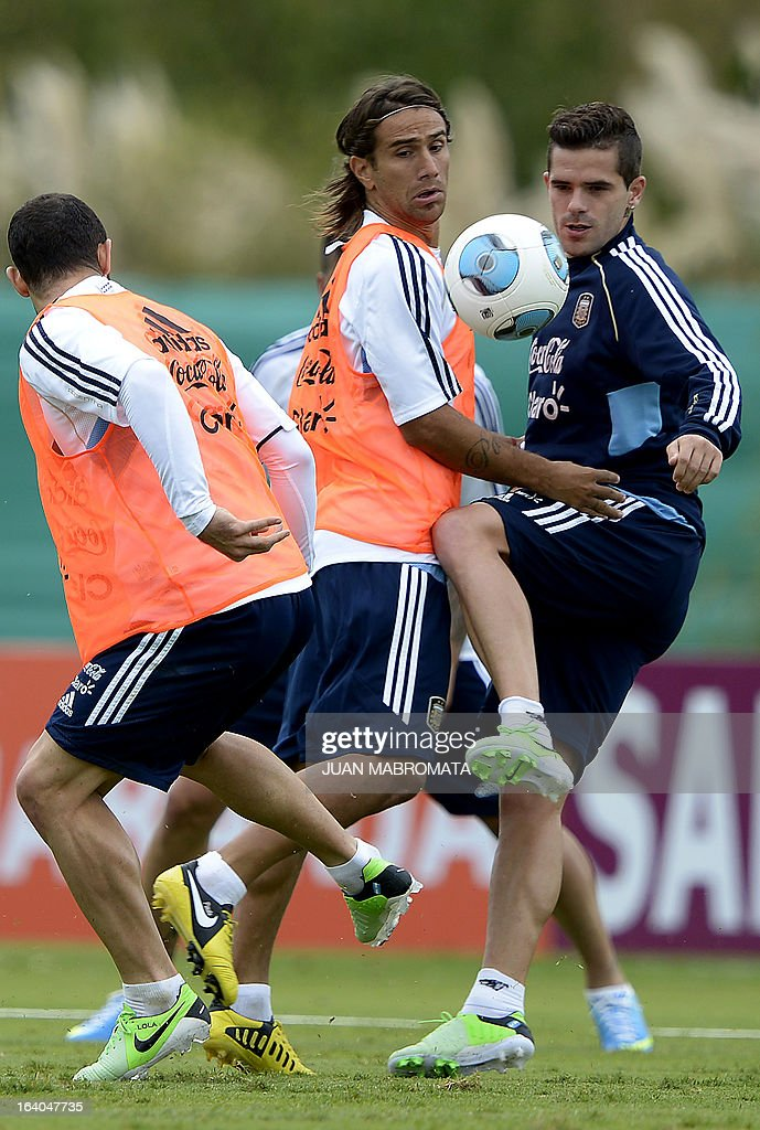 Argentina's midfielder Leonardo Ponzio (C) and midfielder Fernando Gago (R) vie for the ball during a training session in Ezeiza, Buenos Aires on March 19, 2013 ahead of the Brazil 2014 FIFA World Cup South American qualifier football match against Venezuela on March 22. AFP PHOTO / Juan Mabromata