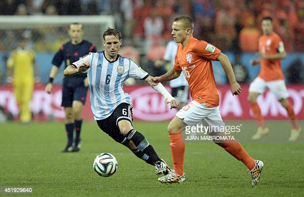 Argentina's midfielder Lucas Biglia and Netherlands' midfielder Jordy Clasie vie for the ball during the semifinal football match between Netherlands...