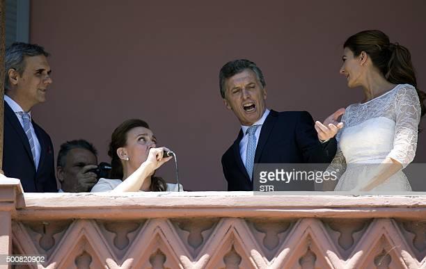 Argentina's new President Mauricio Macri dances next to his wife Juliana Awada and VicePresident Gabriela Michetti on a balcony of the Casa Rosada...