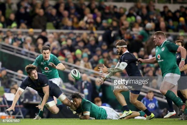 Argentina's number 8 Tomas Lezana offloads as he's tackled by Ireland's centre Bundee Aki during the autumn international rugby union test match...