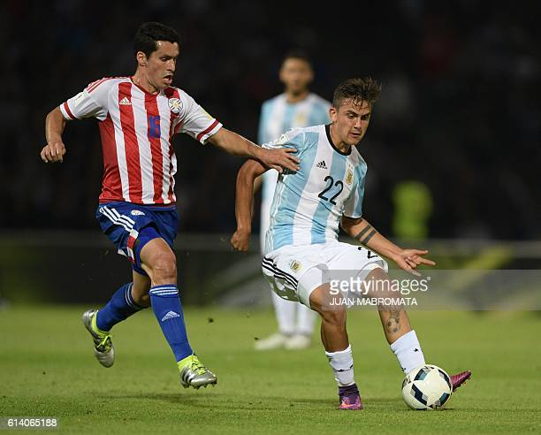 Argentina's Paulo Dybala and Paraguay's midfielder Cristian Riveros vie for the ball during their Russia 2018 World Cup football qualifier match in...