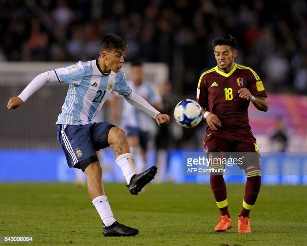 Argentina's Paulo Dybala and Venezuela's Junior Moreno eye the ball during their 2018 World Cup qualifier football match in Buenos Aires on September...