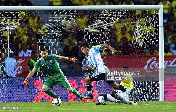 Argentina's Paulo Dybala drives the ball past Colombia's Cristian Zapata as Colombia's David Ospina looks on during their Russia 2018 FIFA World Cup...