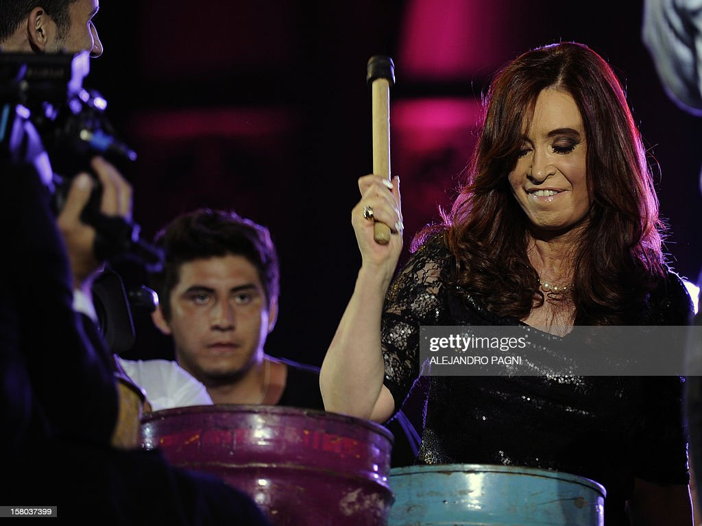 Argentina's President Cristina Fernandez de Kirchner beats a drum with members of the Argentinian music group Choque Urbano at Plaza de Mayo, on December 9, 2012, during a rally called by the government to celebrate the 29th anniversary of the return to democracy in Argentina, on the eve of the Day of Democracy and Human Rights. AFP PHOTO / Alejandro PAGNI