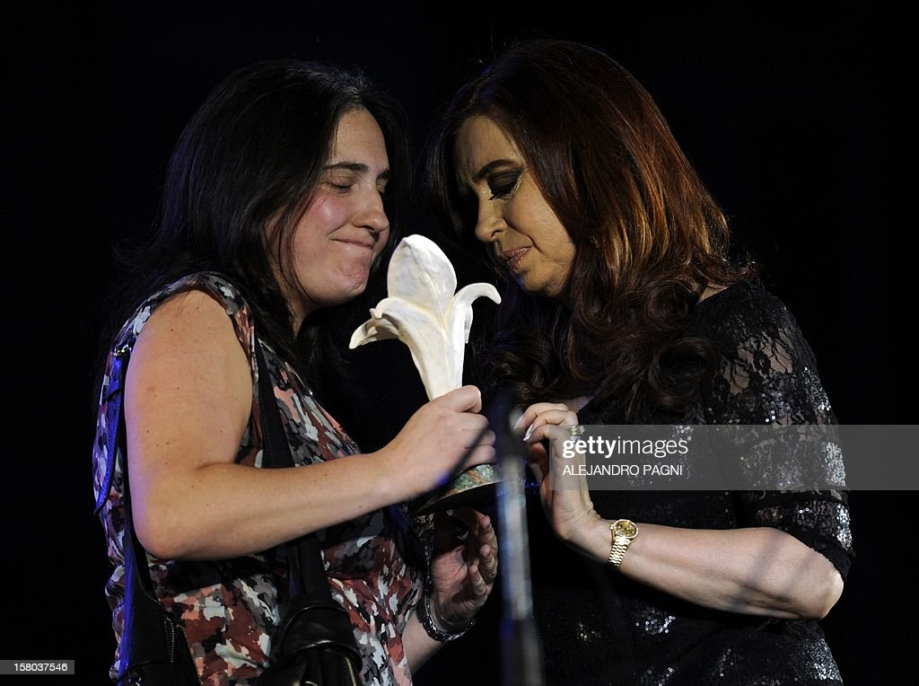 Argentina's President Cristina Fernandez de Kirchner (R) delivers the Azucena Villaflor award to Argentinian writer Juan Gelman (not in frame), and is received by his granddaughter Macarena, at Plaza de Mayo, on December 9, 2012, during a rally called by the government to celebrate the 29th anniversary of the return to democracy in Argentina, on the eve of the Day of Democracy and Human Rights. AFP PHOTO / Alejandro PAGNI