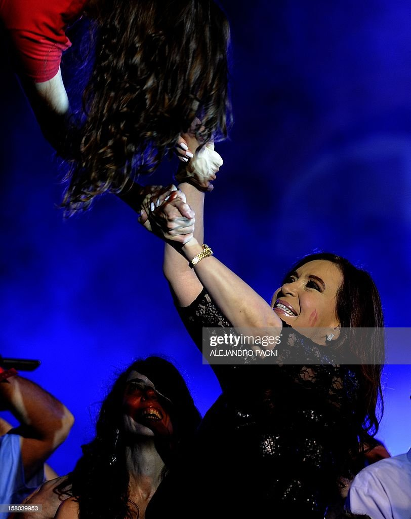 Argentina's President Cristina Fernandez de Kirchner (lower-R) interacts with a member of the Argentinian acrobatic theater group Fuerza Bruta, at Plaza de Mayo, on December 9, 2012, during a rally on the eve of the Day of Democracy and Human Rights, called by the government to celebrate the 29th anniversary of the return to democracy in Argentina. AFP PHOTO / Alejandro PAGNI