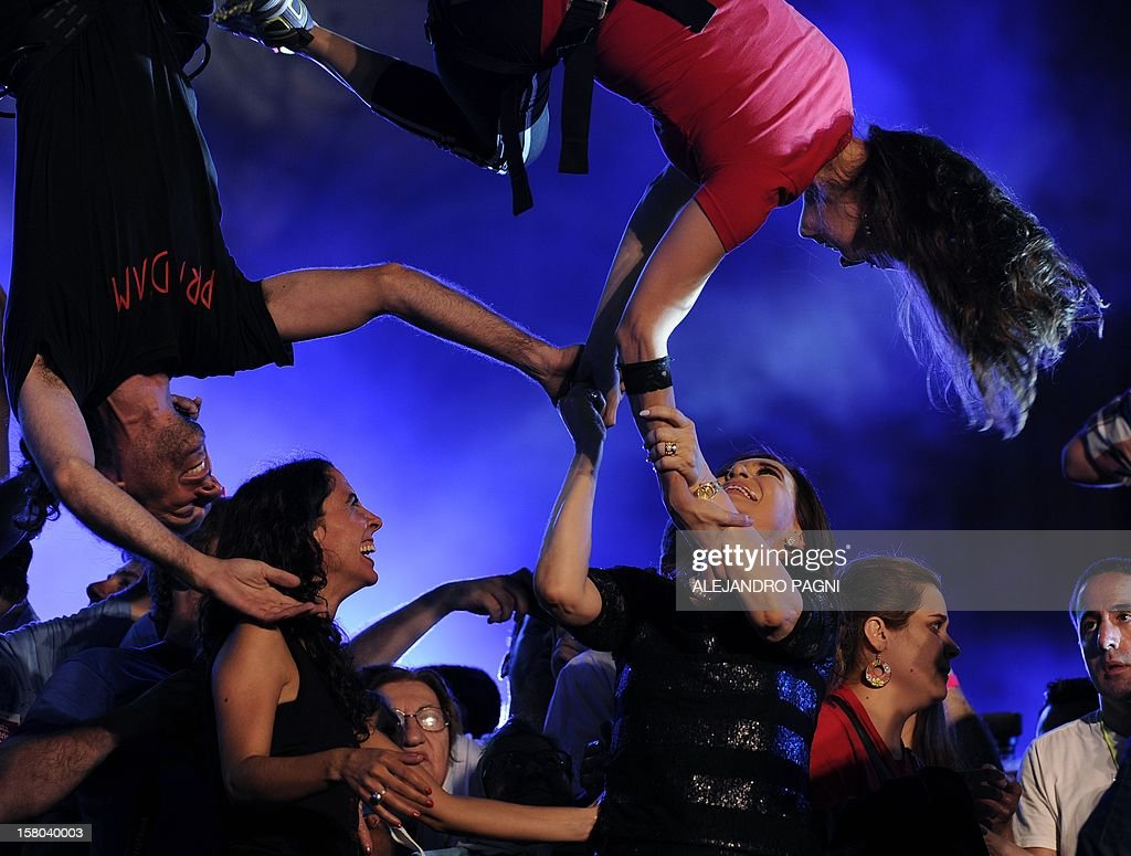 Argentina's President Cristina Fernandez de Kirchner (lower 3R)) interacts with members of the Argentinian acrobatic theater group Fuerza Bruta, at Plaza de Mayo, on December 9, 2012, during a rally on the eve of the Day of Democracy and Human Rights, called by the government to celebrate the 29th anniversary of the return to democracy in Argentina. AFP PHOTO / Alejandro PAGNI