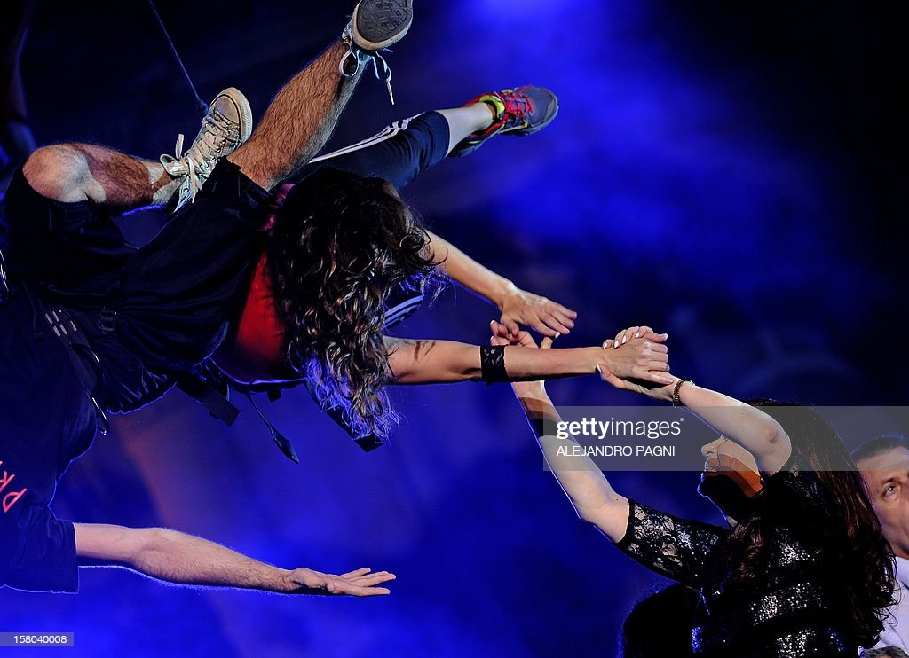 Argentina's President Cristina Fernandez de Kirchner (lower-R) interacts with members of the Argentinian acrobatic theater group Fuerza Bruta, at Plaza de Mayo, on December 9, 2012, during a rally on the eve of the Day of Democracy and Human Rights, called by the government to celebrate the 29th anniversary of the return to democracy in Argentina. AFP PHOTO / Alejandro PAGNI