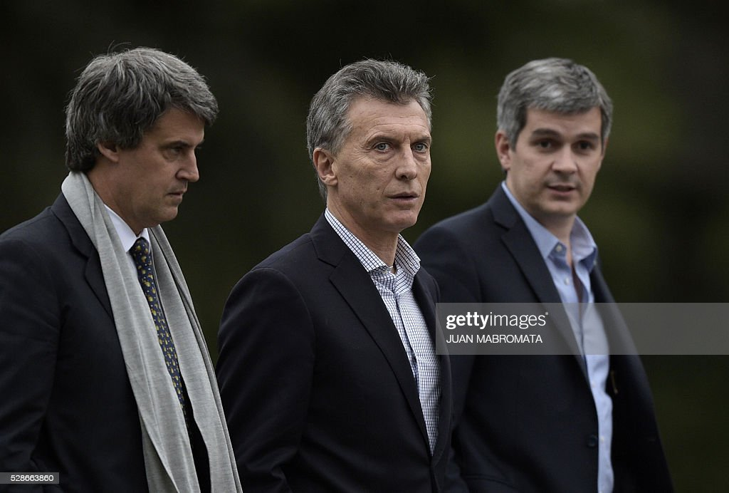 Argentina's President Mauricio Macri (C), Finance Minister Alfonso Prat-Gay (L) and Cabinet Chief Marcos Pena walk in the yard of the presidential residence before give a press conference for the foreign press in Olivos, Buenos Aires on May 6, 2016. / AFP / JUAN