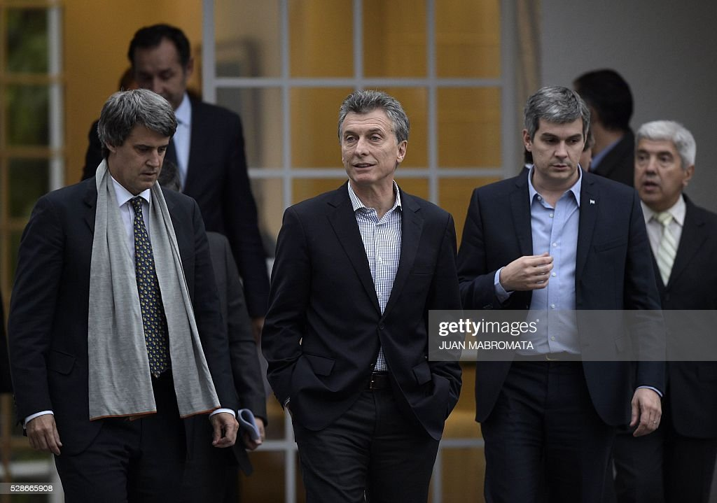 Argentina's President Mauricio Macri (C), Finance Minister Alfonso Prat-Gay (L) and Cabinet Chief Marcos Pena walk in the yard of the presidential residence before giving a press conference for the foreign press in Olivos, Buenos Aires on May 6, 2016. / AFP / JUAN