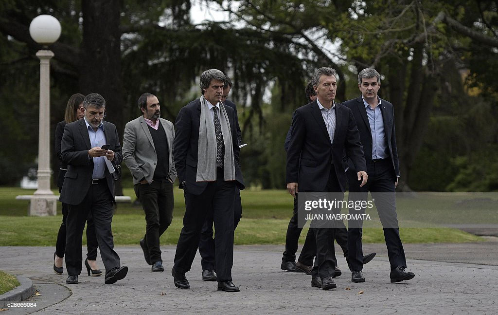 Argentina's President Mauricio Macri (2-R), Finance Minister Alfonso Prat-Gay (3-R) and Cabinet Chief Marcos Pena (R) walk in the yard of the presidential residence before giving a press conference for the foreign press in Olivos, Buenos Aires on May 6, 2016. / AFP / JUAN