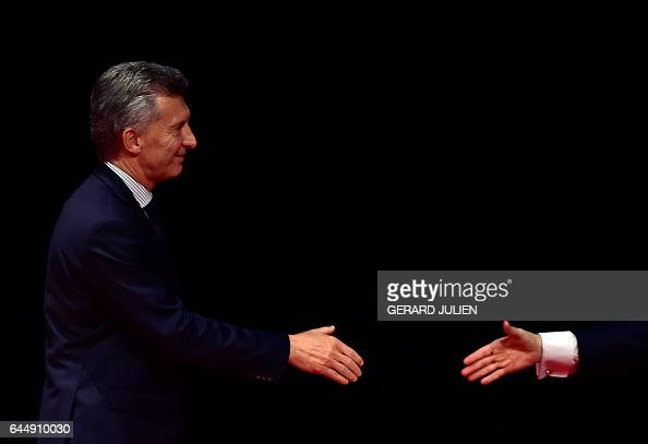 TOPSHOT Argentina's President Mauricio Macri go to shake hands after receiving the Nueva Economia Forum prize for debating during an award ceremony...