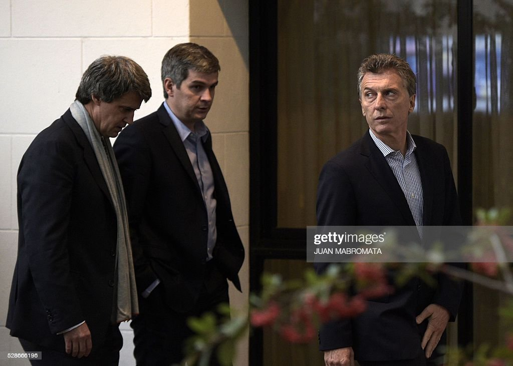 Argentina's President Mauricio Macri (R) is followed by Finance Minister Alfonso Prat-Gay (L) and Cabinet Chief Marcos Pena (C) as they walk in the yard of the presidential residence before giving a press conference for the foreign press in Olivos, Buenos Aires on May 6, 2016. / AFP / JUAN