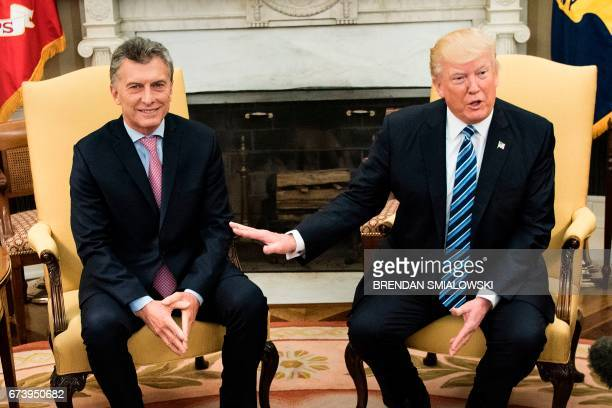 Argentina's President Mauricio Macri listens while US President Donald Trump speaks to the press before a meeting in the Oval Office of the White...