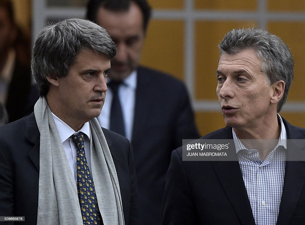 Argentina's President Mauricio Macri (R) speaks with Finance Minister Alfonso Prat-Gay as they walk in the yard of the presidential residence before giving a press conference for the foreign press in Olivos, Buenos Aires on May 6, 2016. / AFP / JUAN