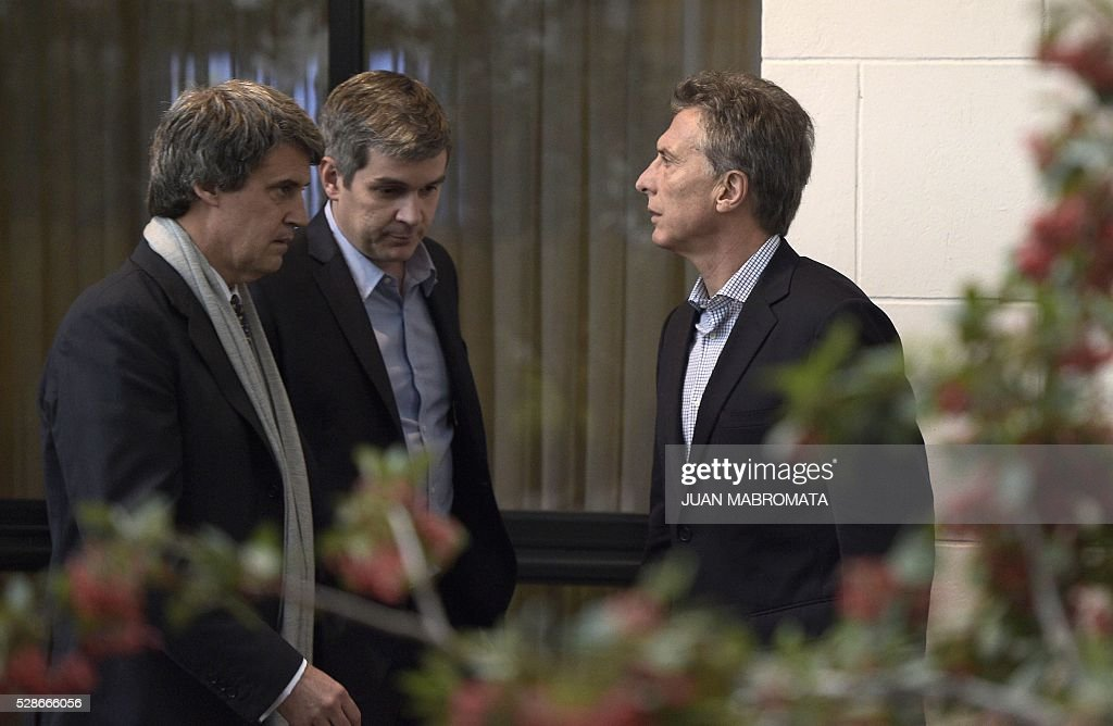 Argentina's President Mauricio Macri (R) speaks with Finance Minister Alfonso Prat-Gay (L) and Cabinet Chief Marcos Pena (C) in the yard of the presidential residence before giving a press conference for the foreign press in Olivos, Buenos Aires on May 6, 2016. / AFP / JUAN