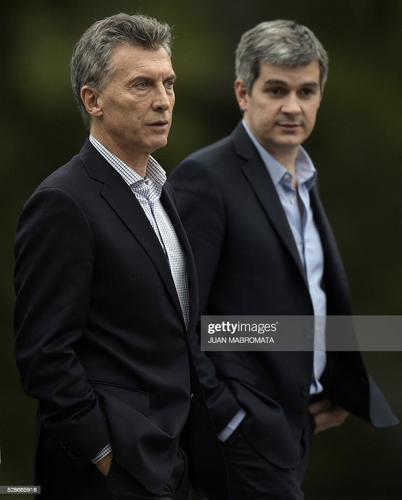 Argentina's President Mauricio Macri (L) walks next to Cabinet Chief Marcos Pena in the yard of the presidential residence before giving a press conference for the foreign press in Olivos, Buenos Aires on May 6, 2016. / AFP / JUAN