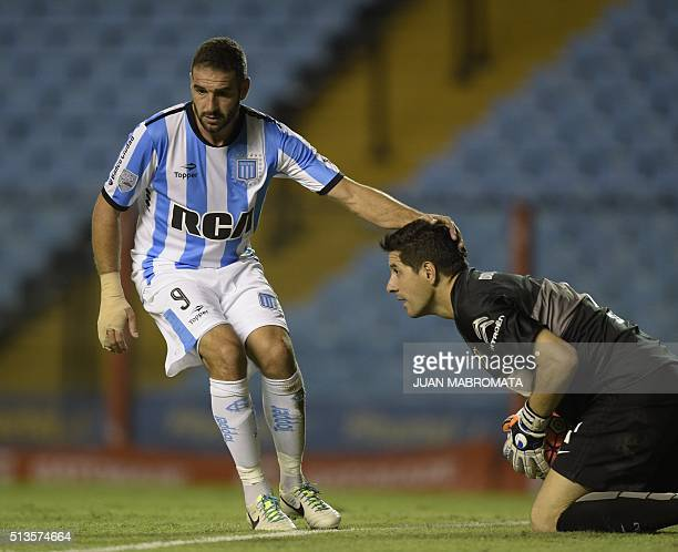 Argentina's Racing Club forward Lisandro Lopez touches the head of Argentina's Boca Juniors goalkeeper Agustin Orion during the Copa Libertadores...