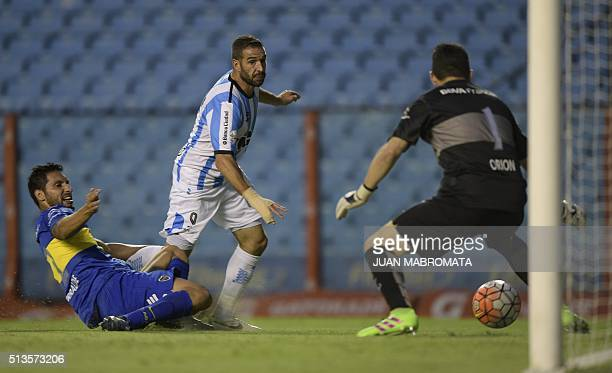 Argentina's Racing Club forward Lisandro Lopez vies for the ball with Argentina's Boca Juniors defender Juan Insaurralde and goalkeeper Agustin Orion...