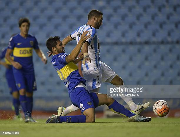 Argentina's Racing Club forward Lisandro Lopez vies for the ball with Argentina's Boca Juniors defender Juan Insaurralde during the Copa Libertadores...