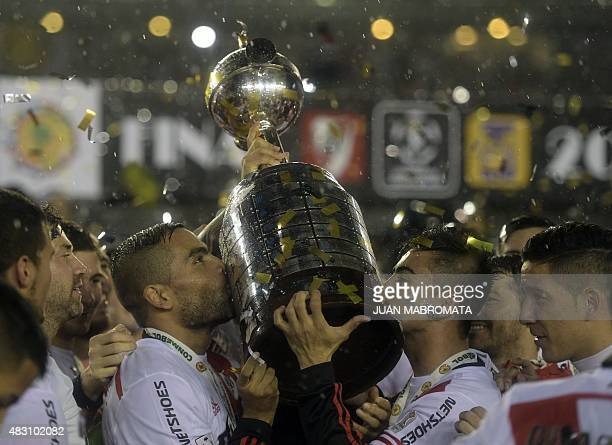 Argentina's River Plate defender Gabriel Mercado and midfielder Gonzalo Martinez kiss the trophy surrounded by teammates after wining the Copa...