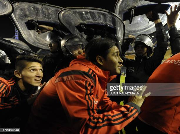 Argentina's River Plate footballers leave the pitch under police shields after the match was suspend when Boca Juniors fans pepper sprayed River...