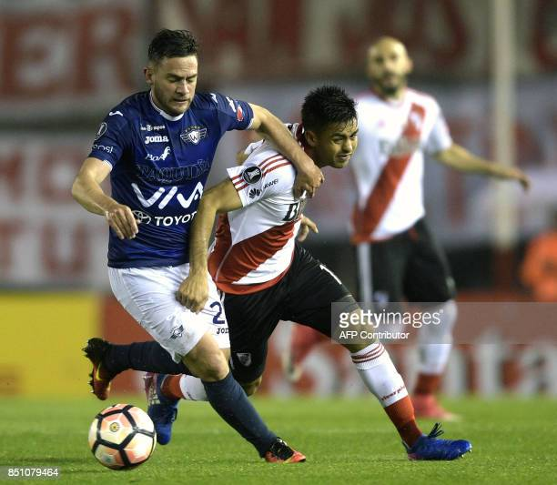 Argentina's River Plate forward Gonzalo Martinez vies for the ball with Bolivia's Wilstermann midfielder Fernando Saucedo during their Copa...