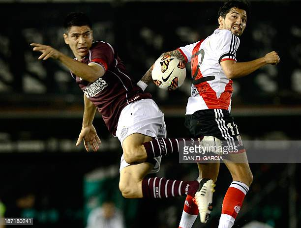 Argentina's River Plate forward Juan Menseguez vies for the ball with Lanus midfielder Jorge Ortiz during their Copa Sudamericana 2013 round before...