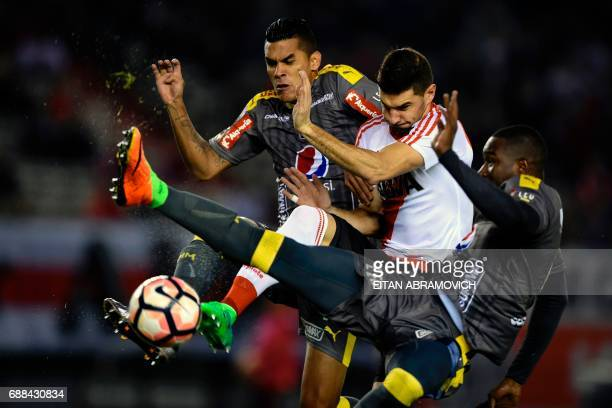 Argentina's River Plate forward Lucas Alario vies for the ball with Colombia's Deportivo Independiente Medellin defender Juan Camilo Saiz and...