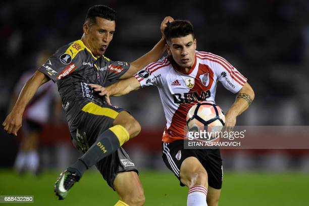Argentina's River Plate midfielder Tomas Andrade vies for the ball with Colombia's Deportivo Independiente Medellin defender Juan Camilo Saiz during...