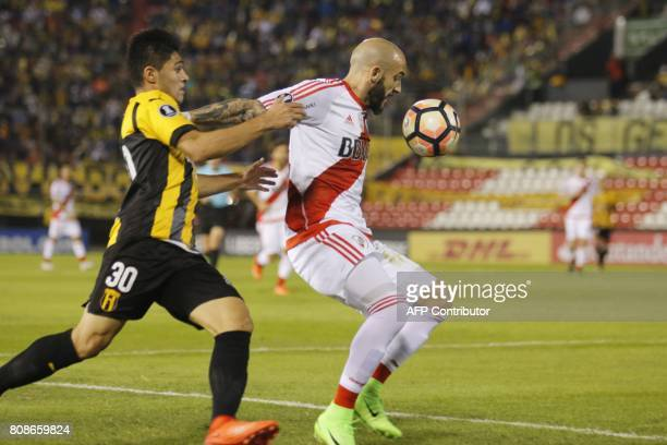 Argentina's River Plate player Javier Pinola vies for the ball with Paraguay's Guarani Antonio Marin during their Copa Libertadores 2017 match at the...