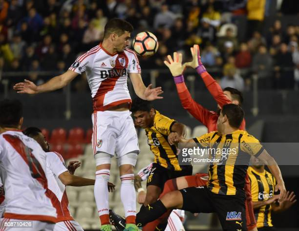 Argentina's River Plate player Milton Casco and Augusto Batalla vie for the ball with Luis de la Cruz of Paraguay's Guarani during their Copa...