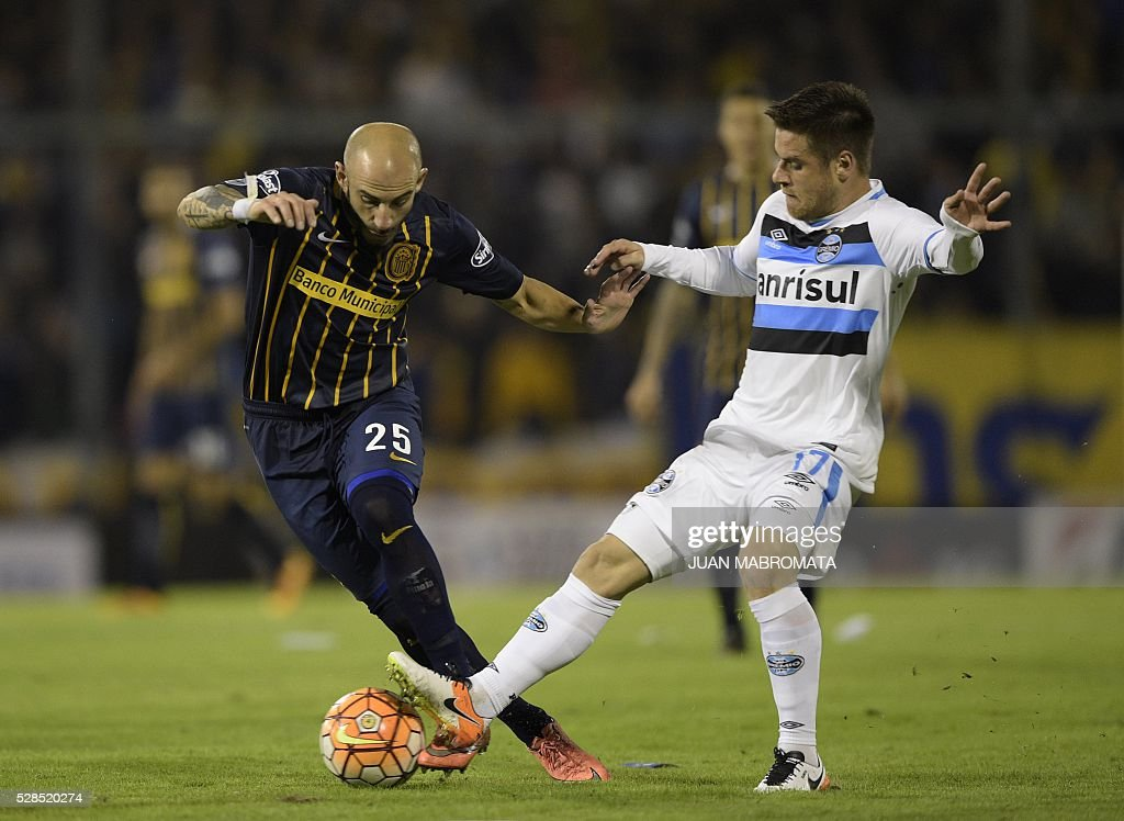 Argentina's Rosario Central defender Javier Pinola (L) vies for the ball with Brazil's Gremio midfielder Ramiro during their Copa Libertadores 2016 round before the quarterfinals second leg football match at the 'Gigante de Arroyito' stadium in Rosario, Santa Fe, Argentina, on May 5, 2016. / AFP / JUAN