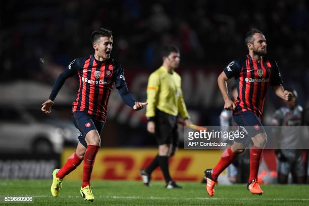 Argentina's San Lorenzo defender Gabriel Hernan Rojas and teammate midfielder Fernando Daniel Belluschi react after defeating Ecuador's Emelec in...
