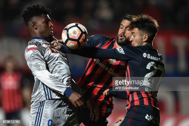 Argentina's San Lorenzo defenders Gabriel Hernan Rojas and Matias Nicolas Caruzzo vie for the ball with Ecuador's Emelec forward Marlon de Jesus...
