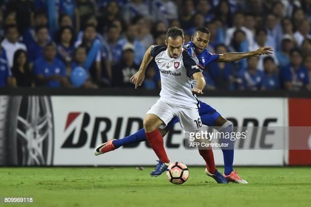 Argentina's San Lorenzo Fernando Belluschi vies for the ball with Eduar Preciado of Ecuador's Emelec during their 2017 Copa Libertadores football...