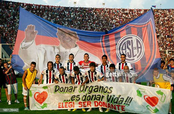 Argentina's San Lorenzo football team poses with a huge flag behind with an image of Pope Francis a member of the club before the start of the match...